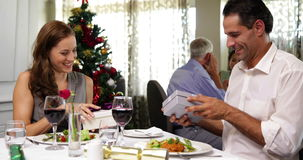 Happy couple having a christmas meal together and exchanging gifts