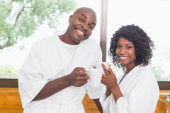 Happy couple having coffee together in bathrobes Royalty Free Stock Photo