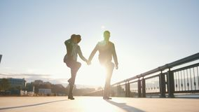 Happy couple having dancing outdoors - male and woman have fun at sunset. Happy couple having fun outdoors - male and woman are dancing at sunset, wide angle stock video
