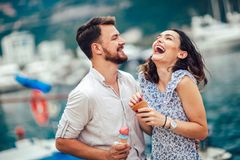 Happy couple having date and eating ice cream on vacation. Sea background stock photo