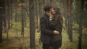 Happy couple having a date in the forest. Smiling man and woman are standing among the trees and embracing each other