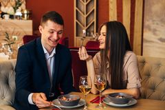 Happy couple having dinner at restaurant and laughing. Leisure, celebration, food and drinks, people and holidays concept - smiling couple having dinner and Stock Image