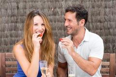 Happy couple having food in garden Stock Images