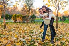 Happy couple having fun in autumn park on a sunny Stock Photography