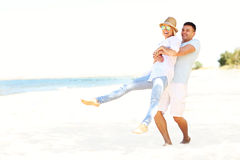 Happy couple having fun at the beach Stock Images