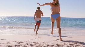 Happy couple having fun at the beach. Slow motion of happy couple having fun at the beach on a sunny stock video footage