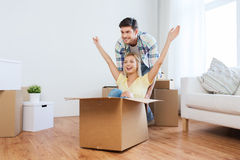 Happy couple having fun with boxes at new home Stock Images