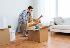 Happy couple having fun with boxes at new home Stock Image
