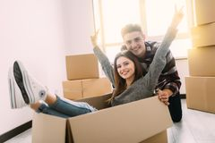 Happy young couple is having fun with cardboard boxes in new house at moving day. stock image