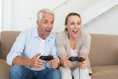 Happy couple having fun on the couch playing video games Stock Image