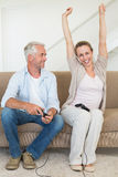 Happy couple having fun on the couch playing video games Stock Photo