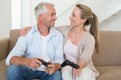 Happy couple having fun on the couch playing video games Royalty Free Stock Photography
