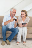 Happy couple having fun on the couch playing video games Stock Photos