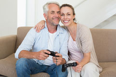 Happy couple having fun on the couch playing video games Stock Photography