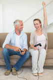 Happy couple having fun on the couch playing video games Royalty Free Stock Image