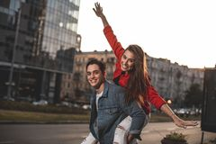Happy couple having fun on date. I believe I can fly. Waist up portrait of young men and women walking on street. Smiling female is sitting on male back with royalty free stock photos