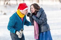 Happy couple having fun and drinking hot tea on rink outdoors. Royalty Free Stock Photography