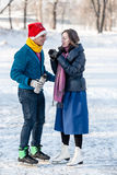 Happy couple having fun and drinking hot tea on rink outdoors. Stock Images
