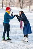 Happy couple having fun and drinking hot tea on rink outdoors. royalty free stock photos