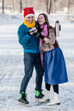 Happy couple having fun and drinking hot tea on rink outdoors. Royalty Free Stock Images
