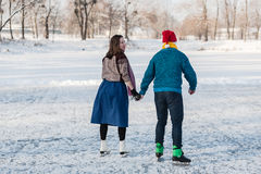 Happy couple having fun ice skating on rink outdoors. Stock Photography