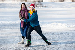 Happy couple having fun ice skating on rink outdoors. Stock Images