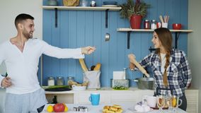 Happy couple having fun in the kitchen fencing with ladle and rolling-pin while cooking breakfast at home. Happy couple having fun in the kitchen fencing with Royalty Free Stock Photo