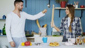 Happy couple having fun in the kitchen fencing with ladle and rolling-pin while cooking breakfast at home. Happy couple having fun in the kitchen fencing with Stock Image
