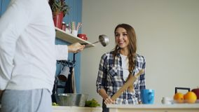 Happy couple having fun in the kitchen fencing with ladle and rolling-pin while cooking breakfast at home. Happy couple having fun in the kitchen fencing with Royalty Free Stock Image