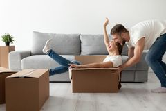 Happy couple having fun playing with cardboard box moving in. Happy couple having fun laughing moving into new home, young excited women riding sitting in Royalty Free Stock Photos