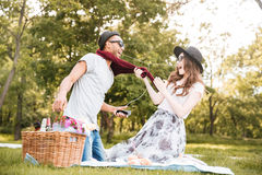 Happy couple having fun and listening to music on picnic. Happy young couple having fun and listening to music from smartphone on picnic Royalty Free Stock Photo