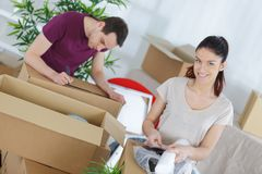 Happy couple having fun while making cardboard boxes stock image