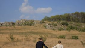 Happy couple having fun on the meadow. couple running around in the field stock footage