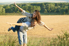 Happy couple having fun on outdoor, girl riding on man back and fly - romantic travel and people concept, summer landscape with wh Royalty Free Stock Photos