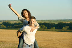 Happy couple having fun on outdoor, girl riding on man back and fly - romantic travel and people concept, summer landscape with wh Royalty Free Stock Photo