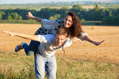 Happy couple having fun on outdoor, girl riding on man back and fly - romantic travel and people concept, summer landscape with wh Royalty Free Stock Image