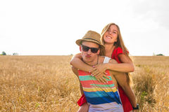 Happy Couple Having Fun Outdoors on wheat field. Laughing Joyful Family together. Freedom Concept. Piggyback Royalty Free Stock Photography