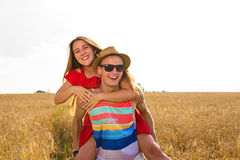 Happy Couple Having Fun Outdoors on wheat field. Laughing Joyful Family together. Freedom Concept. Piggyback Stock Photo