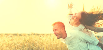 Happy couple having fun outdoors on wheat field. Over sunset Stock Photo