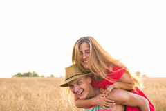 Happy Couple Having Fun Outdoors on wheat field over sunset. Laughing Joyful Family together. Freedom Concept. Piggyback Royalty Free Stock Photography