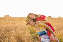 Happy Couple Having Fun Outdoors on wheat field over sunset. Laughing Joyful Family together. Freedom Concept. Piggyback Royalty Free Stock Images