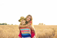 Happy Couple Having Fun Outdoors on wheat field over sunset. Laughing Joyful Family together. Freedom Concept. Piggyback Stock Image