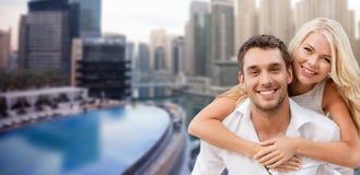 Happy couple having fun over dubai city background Stock Photo