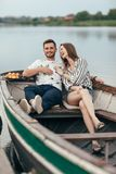 Happy couple having fun relaxing in boat on lake stock images