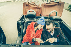 Happy couple having fun with satnav at car travel. Hipster guy having fun with fashion girlfriend at road trip - Love relationship concept stock images
