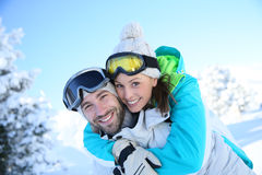 Happy couple having fun on ski slopes stock image