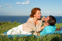 A Happy couple having fun on summer picnic outdoors and smiling.Beautiful couple laying on beach in grass. stock photo