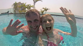 Happy couple having fun in swimming pool. Sending message to friends. Vacation summer. Action camera stock footage