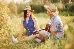 Happy couple having fun together and enjoying together outdoors,  sitting on grass on pier of lake. Boyfriend and girlfriend playi Stock Images