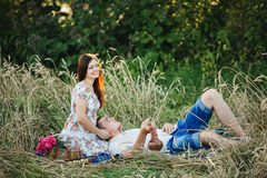 Happy couple having fun together and enjoying together outdoors,  sitting on grass on pier of lake. Boyfriend and girlfriend playi Royalty Free Stock Photos